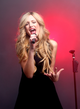 Blonde Rock Star on Stage Singing and Performing Standard-Bild