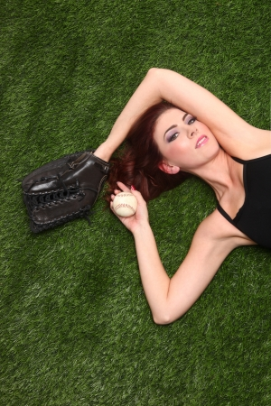 Beautiful Woman Lying in Grass With Baseball Gear Stock Photo - 18349030