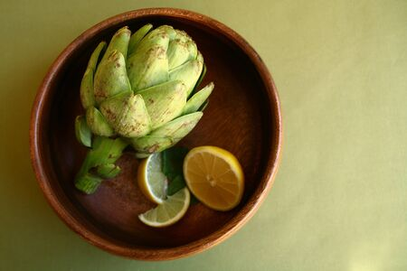 Fresh Artichoke in Wooden Bowl With Lemons Stock Photo - 19485710