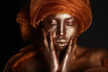 African Amercian Woman Painted With Gold  photo