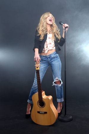 Beautiful Woman Singing on Stage With Mic and Guitar photo