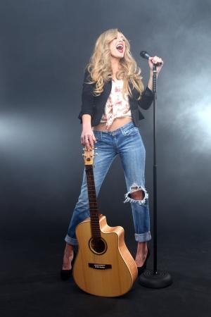 cantando: Mujer hermosa que canta en el escenario con micr�fono y guitarra