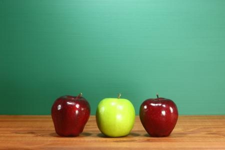 Three School Apples Sitting on Teacher Desk