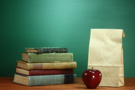 sac: Back to School Books, Apple and Lunch on Teacher Desk Stock Photo