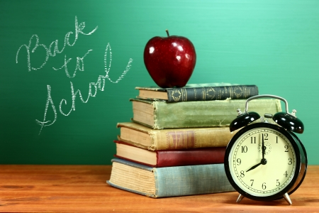 returning: Back to School Books, Apple and Clock on Desk Stock Photo
