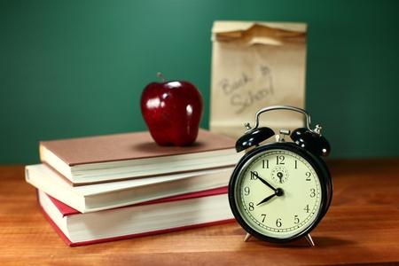 punctual: Manzana Reloj y pila de libros sobre un escritorio de Regreso a la Escuela