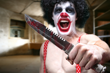 Knife Wielding Horror Clown in Condemned Building photo