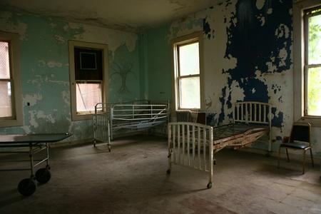 空の錆びたベッドで放棄された病院の建物