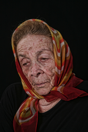 Unhappy Elderly Old Woman on Black Background
