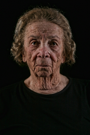 grieving: Unhappy Elderly Old Woman on Black Background
