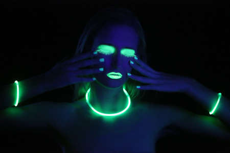 uv: Beautiful Woman Wearing UV Cosmetics Under Black Light Stock Photo