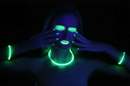 black light: Beautiful Woman Wearing UV Cosmetics Under Black Light Stock Photo