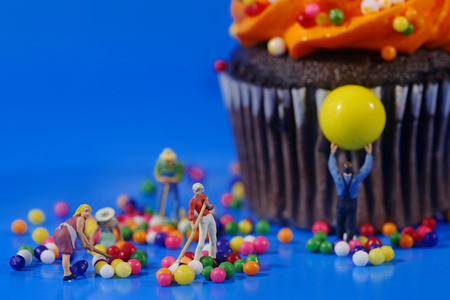 Miniature Plastic People Cleaning Up a Messy Cupcake Stock Photo