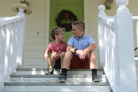 front porch: Happy Sibling Brothers Sitting on the Front Porch Stock Photo