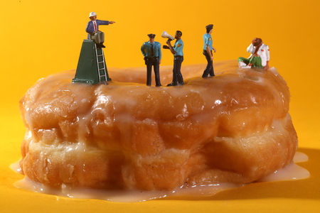 Miniature Police Officers in Conceptual Food Imagery With Donuts Reklamní fotografie