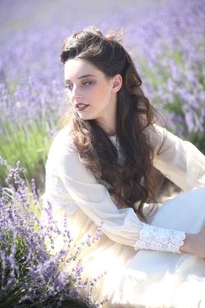 Beautiful Young Girl Outdoors in a Lavender Flower Field Foto de archivo