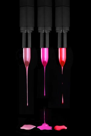 lip stick: Colorful Dripping Lipsticks on a Black Background Stock Photo