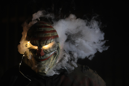 Freightening Man Wearing a Mask With Smoke and Lights