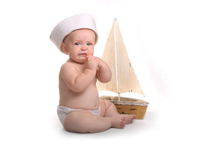 Crying and Sad Baby Sitting up Wearing Sailor Hat on White Background