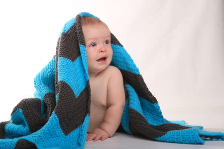 Adorable Baby Smiling Lying on Stomach With Blanket on White Background