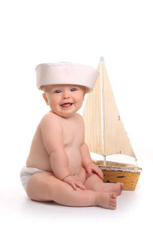 Happy Baby Toddler Sitting up Wearing Sailor Hat on White Background
