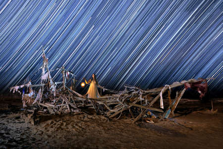 Girl Light Painted on a Ghost Ship With Star Trails on Beach