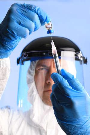 Worker in Biohazard Gear Drawing Vaccine Medication Wearing Gloves Фото со стока