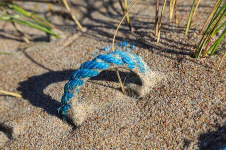 Old blue rope hidden in the sand of a beach
