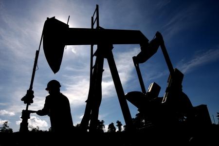 oil  rig: Silhouette di lavoratore controllare una piattaforma petrolifera in limpido cielo azzurro