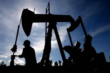 oil worker: Silhouette of worker checking an oil rig under bright blue sky