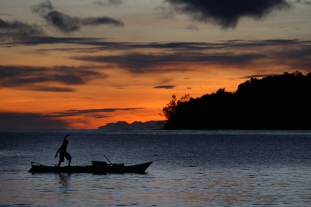 rowboat: Silhouette of fisherman on the boat during early morning gold sky sunrise of Raja Ampat Papua