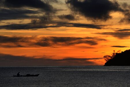 papua: Silhouette of fisherman on the boat during early morning gold sky sunrise of Raja Ampat Papua