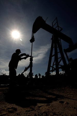 sucker rod pump: Silhouette of worker checking an oil rig under bright blue sky  Stock Photo