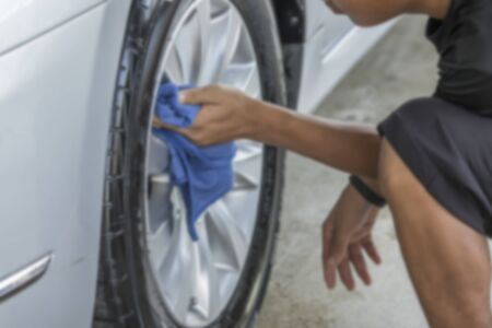 rag wheel: Blurry image, Man was wiping car wheel with hand and microfiber cloth, Car cleaning, Car washing Stock Photo