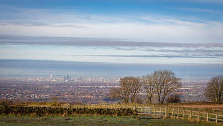 View of Manchester city with hazy winter sky, from Werneth Low Country Park on the borders of Stockport and Tameside, Greater Manchester.