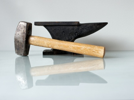 Blacksmith tools, a hammer and an old anvil on a glass plate with white background  photo