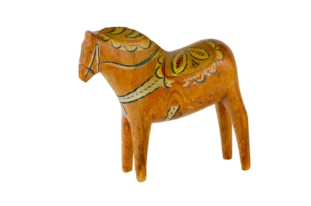 An old Dalecarlian or Dala Horse carved by hand  Originally a toy for children, and this one is used by several generations of children in my family, now a national symbol of Sweden  Isolated on white background  photo