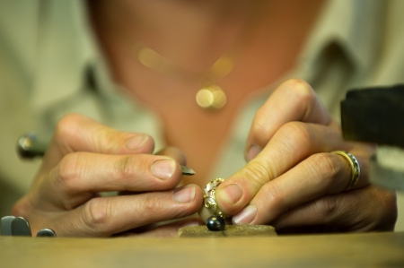 Uppsala, Sweden - August 27, 2013  The goldsmith at work, a closeup when she is preparing a ring for a stone