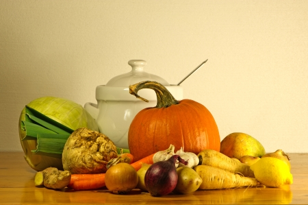 The beauty of fall as a still life with soup vegetables and a soup tureen on a wooden table photo