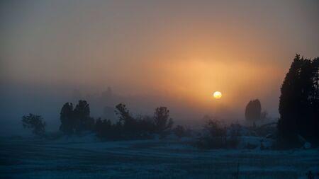 sweden in winter: Sunset in the foggy winter evening in Uppland, Sweden