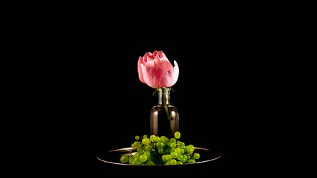 Rose and grapes, a still life, on a steel plate with black backround.