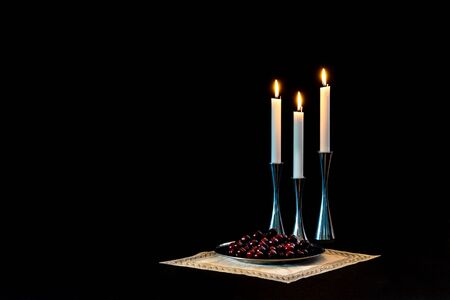 Cherries and candles in steel on a table cloth, a still life.