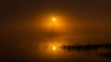 Sunrise over the lake in a foggy morning. Halsingland, Sweden
