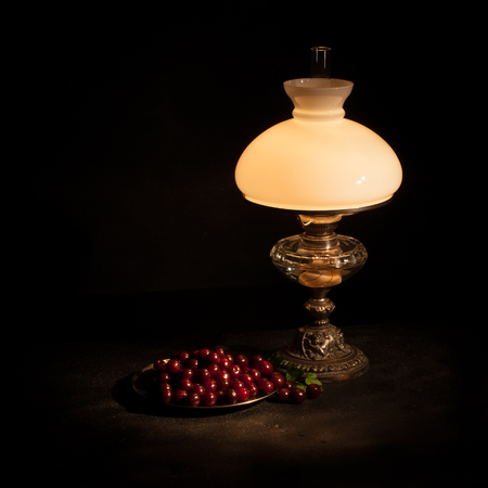 The Kerosene lamp and a plate cherries as a still life