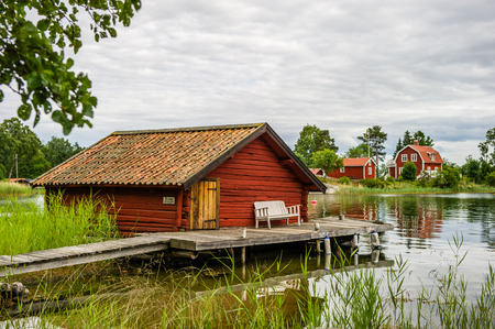 The old timbered boathouse with the liars bench on the bridge in the northern part of Stockholm archipelago, Bjorko-Arholma, Marum Editorial