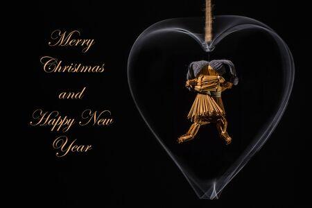 回転する金属の心で踊るわら人形とテキストでクリスマスの挨拶:ストローゴールドカラーでメリークリスマスとハッピーニューイヤー