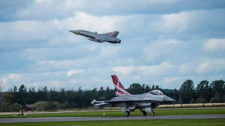 Uppsala, Uppsala län/Sweden - 08/25/2018: Swedish J35 Draken and Danish F16 Fighting Falcon in action:         A flypast or flyover with the retired Swedish fighter J35 Draken over the taxing Danish F16 Falcon at the Swedish Airforces showday at Uppsala
