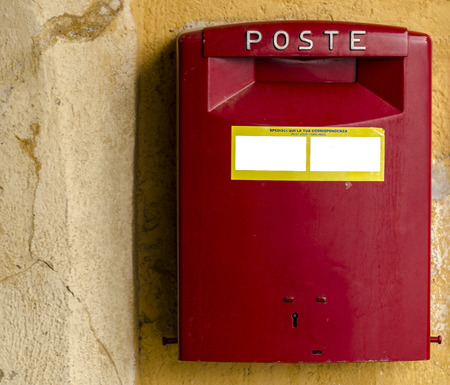 red post box on yellow wall