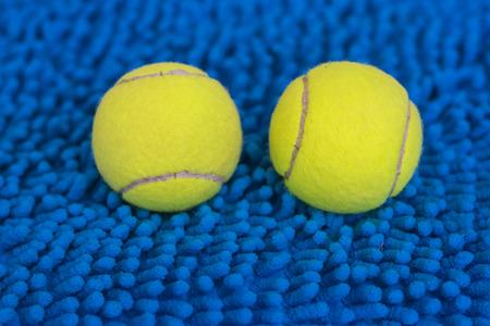 Tennis ball put on the blue wool doormat