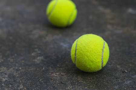 Tennis ball on the dirty ground after playing at the court for exercise or for fun.